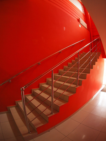 Corridor with red walls and a staircase with steps to the second floor inside the building with wide angle distortion view