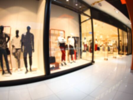 Defocused and blurred image of a large shopping mall hall with glass display cases and mannequins with wide angle fisheye lens and distortion view. The image was blurry for use as background