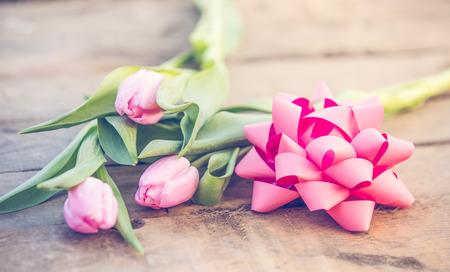 Photo pour Pink tulips on rustic wooden table romantic background - image libre de droit