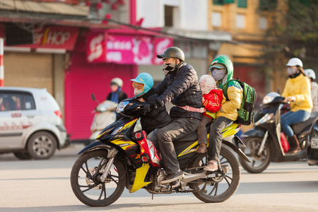 Hanoi, Vietnam-December 17, 2013. Father rides the motorbike with three kids to the school early morning on December 17, 2013 in Hanoi city and it is common scene in Vietnam.