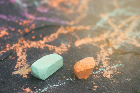 Photo for Two small green and orange piaces of chalk on a sidewalk surface close up view - Royalty Free Image