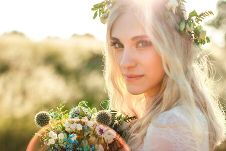 Photo pour Beautiful young woman portrait in a white dress in boho style with a floral wreath in the summer in the field. Selective soft focus. - image libre de droit