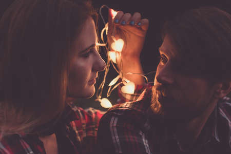 Photo pour Evening romantic date. Caucasian couple in shirts, attractive woman and beard man lookin each other, faces lit by the light of garland with heart shaped bulbs. - image libre de droit