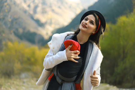 Photo pour Beautiful young mother with her infant baby in sling outdoor. Woman is carrying her child and travel in autumn mountain. Babywearing concept - image libre de droit