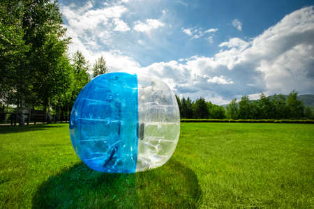 Photo pour Zorbing Balloon on the summer lawn. inflatable zorb ball outdoor. Leisure activity concept with copy space. - image libre de droit