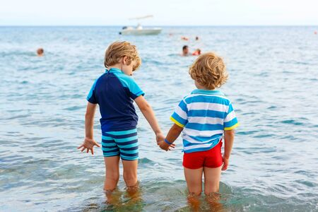 Two little blond kids boys having fun by taking bath in ocean or sea. Funny siblings, children holding hands. Vacations, summer, travel concept. Twins enjoying summer vacations on sea.