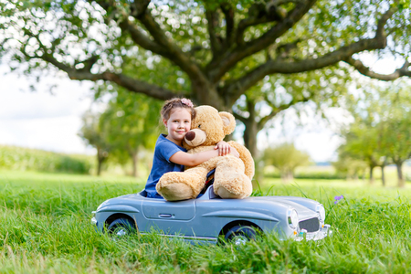 Little preschool kid girl driving big toy car and having fun with playing with big plush toy bear