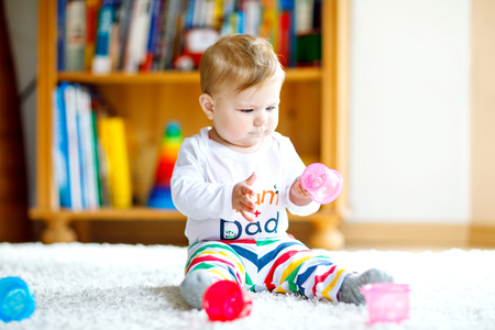 Photo pour Adorable baby girl playing with educational toys in nursery. Happy healthy child having fun with colorful different toys at home. Baby development and first steps, learning to play and to grab - image libre de droit