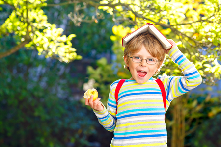 Photo for Happy little preschool kid boy with glasses, books, apple and backpack on his first day to school or nursery. Funny healthy child outdoors on warm sunny day, Back to school concept. Laughing boy. - Royalty Free Image