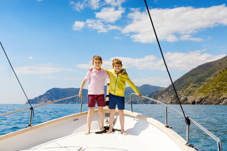 Photo for Two little kid boys, best friends enjoying sailing boat trip. Family vacations on ocean or sea on sunny day. Children smiling. Brothers, schoolchilden, siblings, best friends having fun on yacht. - Royalty Free Image