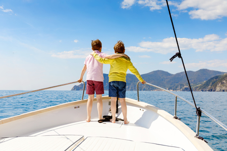 Photo pour Two little kid boys, best friends enjoying sailing boat trip. Family vacations on ocean or sea on sunny day. Children smiling. Brothers, schoolchilden, siblings, best friends having fun on yacht. - image libre de droit