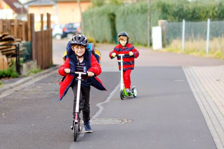 Photo for Two little kids boys riding on push scooters on the way to or from school. Schoolboys of 7 years driving through rain puddle. Funny siblings and best friends playing together. Children after school - Royalty Free Image