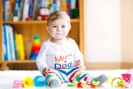 Photo pour Adorable baby girl playing with educational toys in nursery. Happy healthy child having fun with colorful different toys at home. Baby development and first steps, learning to play and to grab. - image libre de droit