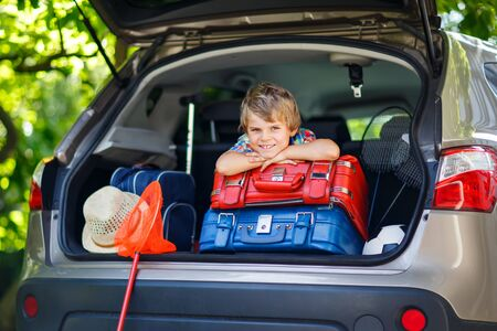 Photo pour Little kid boy sitting in car trunk just before leaving for vacation - image libre de droit