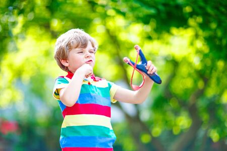 Photo pour Funny little kid boy shooting wooden slingshot against green tree background. Child having fun in summer - image libre de droit