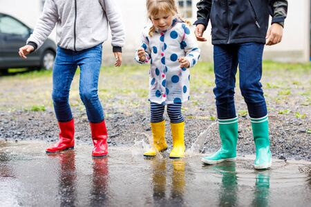 Photo for Close-up of three children, toddler girl and two kids boys wearing red, yellow and green rain boots and walking during sleet. Happy siblings jumping into puddle. Having fun outdoors, active family - Royalty Free Image
