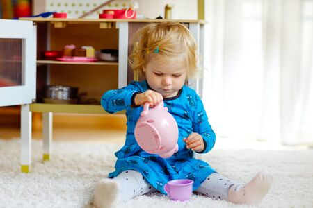 Photo for Adorable cute little toddler girl playing with toy kitchen Happy healthy baby child having fun with role game, playing with crockery teapot at home or nursery. Active daughter with toy. - Royalty Free Image