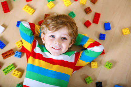 Photo pour Little blond child playing with lots of colorful plastic blocks indoor. Kid boy wearing colorful shirt and having fun with building and creating - image libre de droit