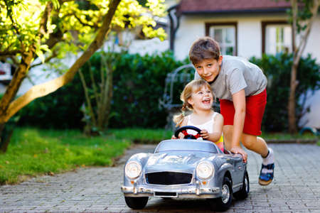 Photo pour Two happy children playing with big old toy car in summer garden, outdoors. Kid boy pushing and driving car with little toddler girl, cute sister inside. Laughing and smiling kids. Lovely family - image libre de droit