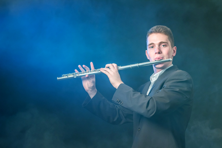 A young musician plays music on a flute. Blue illumination. Smoke against a dark background like fog. Copy space.