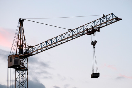 Photo for Construction tower crane with a load against the background of the evening sky - Royalty Free Image