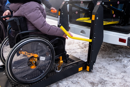 Photo pour A man presses a button on the control panel to pick up a woman in a wheelchair in a taxi for the disabled. Black lift specialized vehicle for people with disabilities. Yellow handrail. Winter time. - image libre de droit