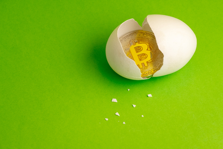 Photo for Gold Bitcoin coin in a broken egg. White eggshell with cryptocurrency symbol inside instead of yolk. Bit-coin birthday concept. Green background. Copy space. - Royalty Free Image