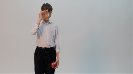Photo pour A student dressed in a white shirt and black pants is holding an apple in one hand, while the other straightens his glasses. Light background. Back to school. Copy space. - image libre de droit
