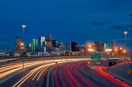 Denver Skyline at dusk with car trails along Interstate 25 in Colorado