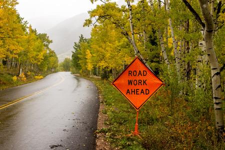 Orange traffic sign warning traffic of Road work ahead on mountain roads