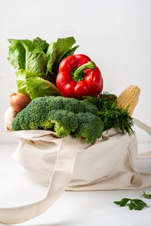 Fabric eco bag full of different fresh vegetables on a light