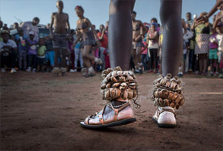 Photograph of Zulu Traditional Dancers with main focus on the feet of the lead dancer with rattle seeds around his ankles with a group of spectators