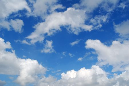 Section of blue sky with puffy clouds