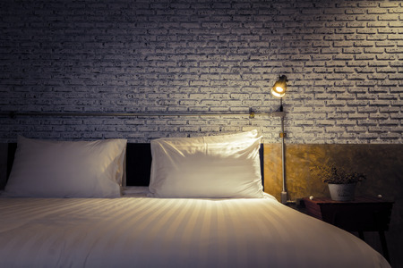 Close up of a bed with lamp light