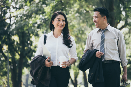 Photo pour Happy Asian business man and woman walking and talking in the public park after finish work. - image libre de droit