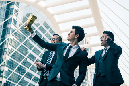 Photo for Happy Asian business people with golden trophy cup for their winner in business project. Teamwork  and success concept - Royalty Free Image