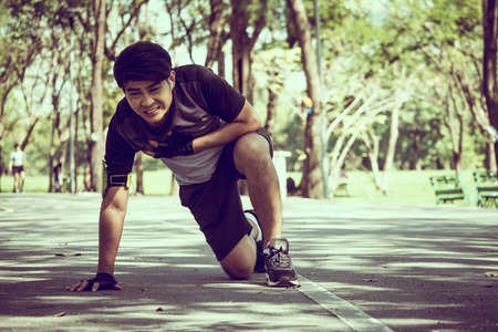 An Asian man has a heart pain while exercising in a park.