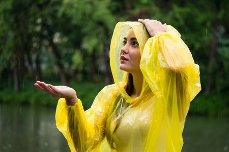 Photo for Young beautiful happy woman in yellow raincoat enjoying the rain - Royalty Free Image