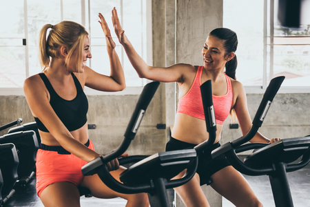 Photo pour Attractive young women working out together on exercise bike at the gym. - image libre de droit