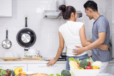 Photo for Couple preparing food for dinner in kitchen at home - Royalty Free Image