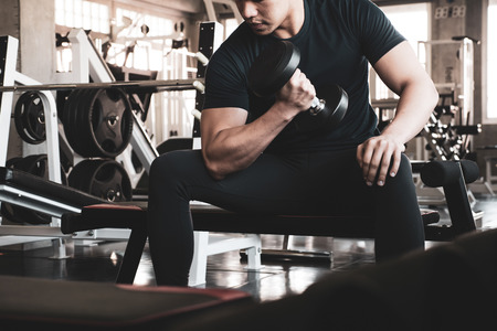 Photo pour Young man exercising building muscles at the gym - image libre de droit