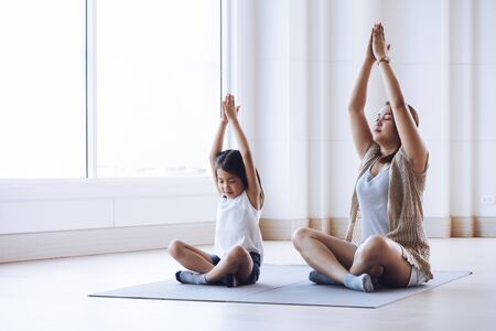 Photo pour Asian mother and her kid daughter doing stretching exercise at home - image libre de droit