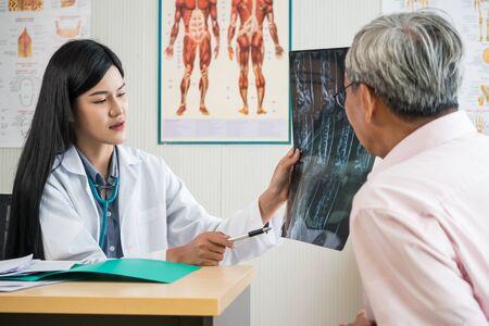 Foto de Expert doctor examining and explaining x-ray film to elderly patient in medical office - Imagen libre de derechos