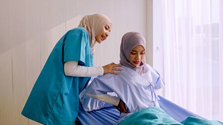 Photo pour Muslim female physiotherapist taking care of patient at hospital room. - image libre de droit