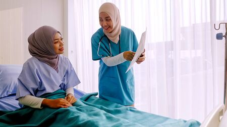 Photo pour Muslim female doctor analysing disease to patient at hospital room. - image libre de droit