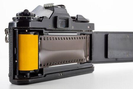 Photo pour Single lens reflex camera and a film roll on a white background. - image libre de droit