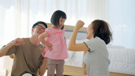 Foto de Happy family with mother, father and disabled daughter having fun dancing together at home. - Imagen libre de derechos