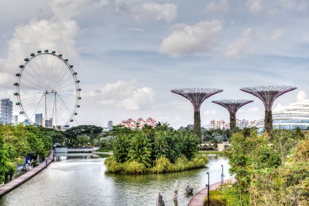 HDR rendering of Singapore at Marina Bay where the Singapore Flyer ferris wheel and Supertree Grove are iconic of the garden city.