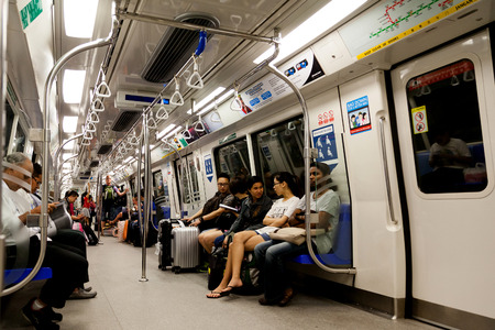 Commuters inside the cabin of a metro train known as Mass Rapid Transit MRT. Singapore's extensive train system spans almost the entire country.