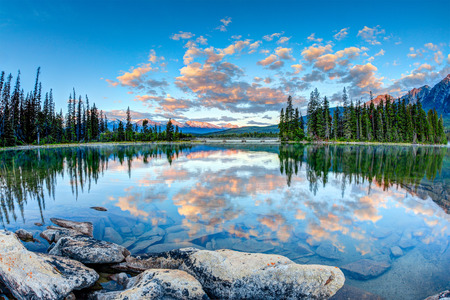 First glimpse of golden sunrise at Pyramid Lake in Jasper National Park, Alberta, Canada. The clouds reflect off the calm waters.